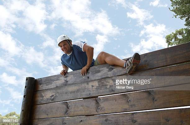 Man climbing over obstacle course