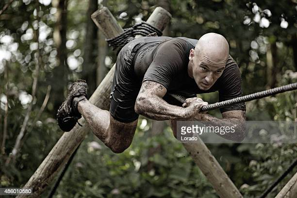 man climbing rope over mud obstacle - obstacle course stock photos and pictures