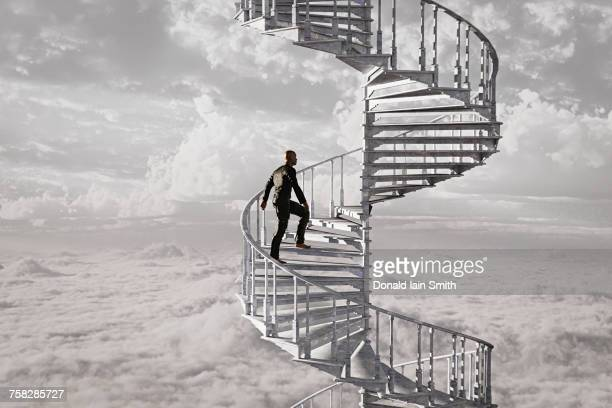 Man climbing spiral staircase in the clouds