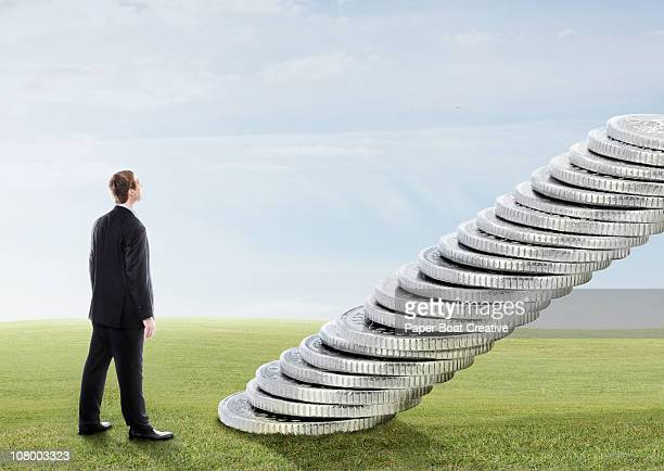 Man climbing stairs made out of silver coins
