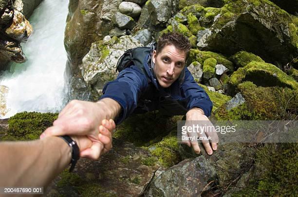 Man climbing steep rocks beside river, grabbing woman's hand