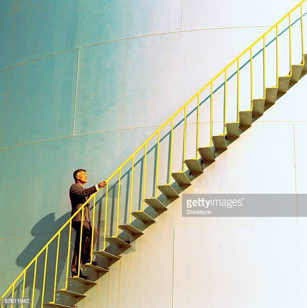 man climbing the stairs to a storage tank - storage tank stock photos and pictures