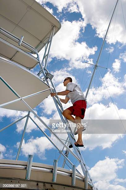 Man climbing to boat tower, side view