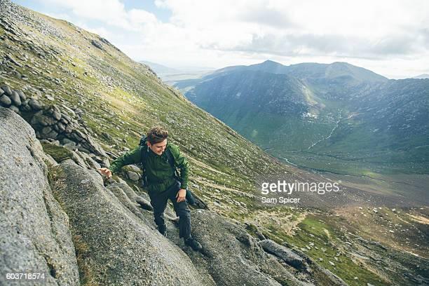 man climbing to mountain summit, scotland - スクランブリング ストックフォトと画像