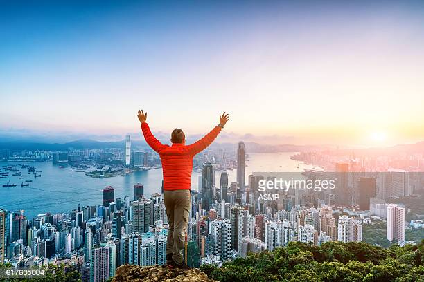 man climbing to the rock facing Hong Kong skyline