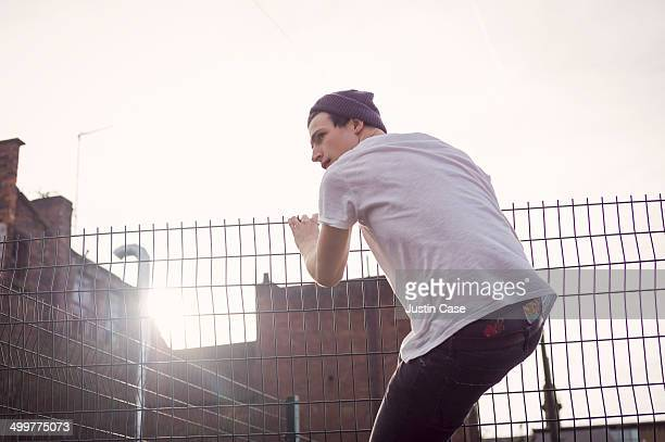 man climbing up a fence in a sun flare