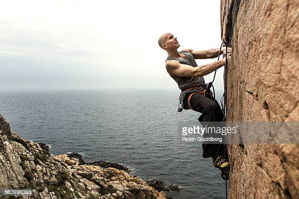Man climbing up cliff with ocean in background