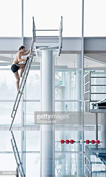 Man climbing up to a highboard in a indoor swimming pool