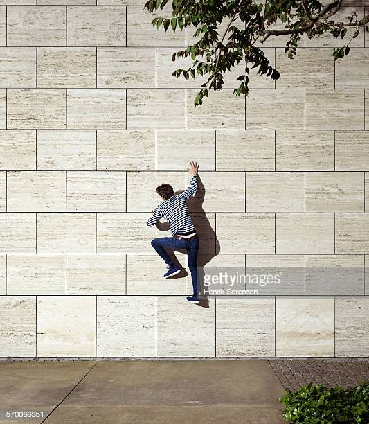man climbing wall - down blouse stock pictures, royalty-free photos & images