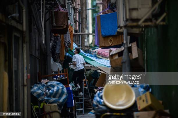 Man climbs a ladder in an alleyway in the Sham Shui Po district of Kowloon in Hong Kong on January 27 one of the international business hub's poorest...