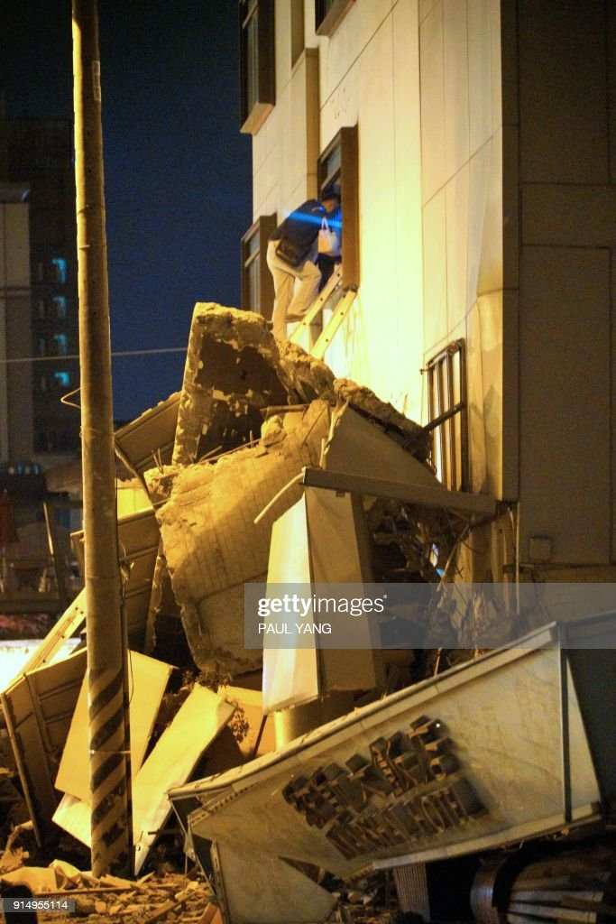 A man climbs a ladder over rubble at the damaged Marshal Hotel in Hualien, eastern Taiwan early February 7, 2018, after a strong earthquake struck the island. A hotel on the east coast of Taiwan has collapsed after a 6.4-magnitude earthquake, the government said. / AFP PHOTO / PAUL YANG / Taiwan OUT