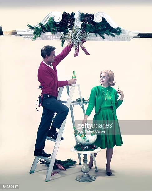 A man climbs a ladder to prepare a holiday wreath while a woman stands below reaching for a bottle of Squirt soda pop ca1950s United States