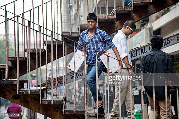 A man climbs a set of stairs carrying a pair of boxed Intex Technologies India Ltd speakers in Nehru Place IT Market a hub for the sale of electronic...