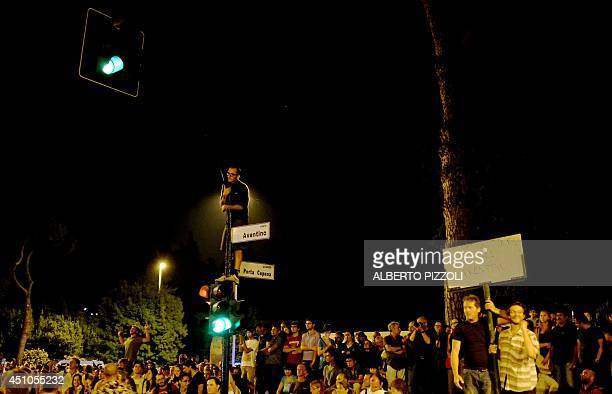 A man climbs a street light outside the area of Circus Maximus hoping to catch a free glimpse of the Rolling Stones concert in Rome on June 22 2014...