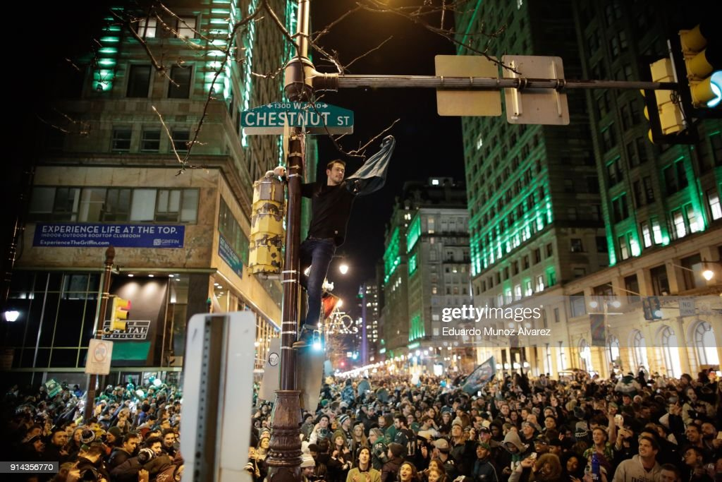 A man climbs a traffic pole as Philadelphia Eagles fans celebrate victory in Super Bowl LII against the New England Patriots on February 4, 2018 in Philadelphia, Pennsylvania..
