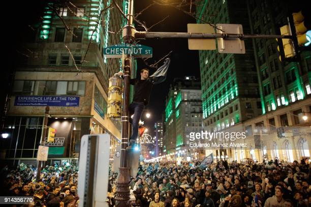 Man climbs a traffic pole as Philadelphia Eagles fans celebrate victory in Super Bowl LII against the New England Patriots on February 4, 2018 in...