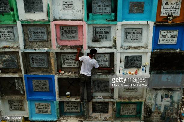 A man climbs atop tombs to replace a candle of their relatives in a cemetery during the commemoration of All Saints' Day in Manila on November 1 2018...