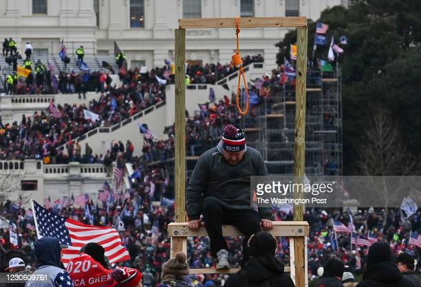 Man climbs down after being photographed with a noose during a protest calling for legislators to overturn the election results in President Donald...