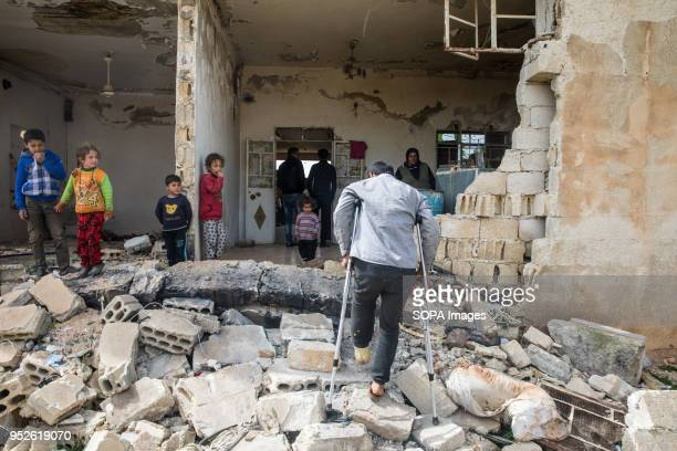 A man climbs into an empty home that his family resettled after being displaced by the conflict in Afrin An estimated 400000 refugees fleeing the...