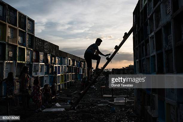 A man climbs on a ladder to reach a tombtone at a public cemetery on November 1 2016 in Manila Philippines Filipinos flock to cemeteries around the...