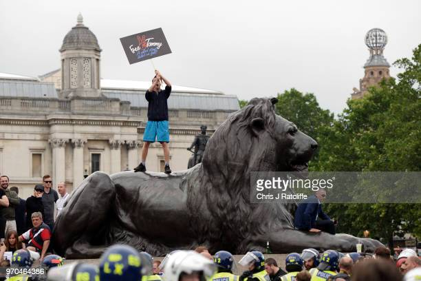 A man climbs on one of the lions in Trafalgar Square as demonstrators clash with police during a 'Free Tommy Robinson' protest on Whitehall on June 9...