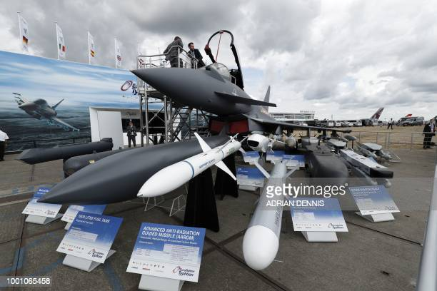 A man climbs out of the cockpit of a Eurofighter Typhoon aircraft at the BAE Systems exhibition space during the Farnborough Airshow south west of...