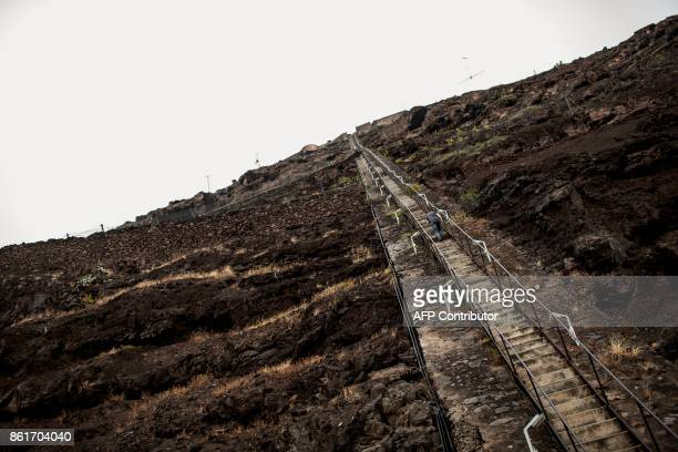 A man climbs the 699 steps of Jacob's ladder in Jamestown the capitol in the tropical island of Saint Helena in the South Atlantic Ocean and part of...