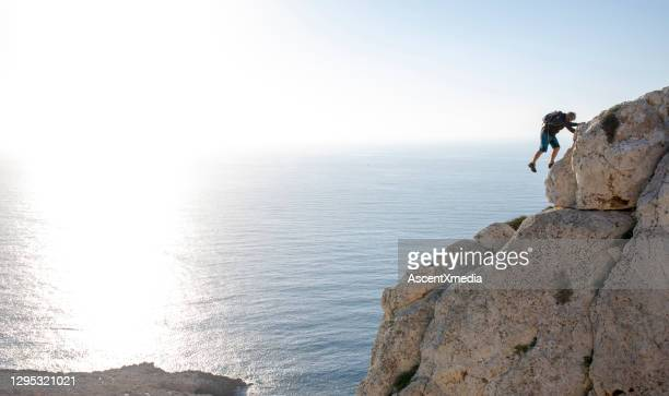 man climbs up coastal rock in the morning - horizon over water stock pictures, royalty-free photos & images
