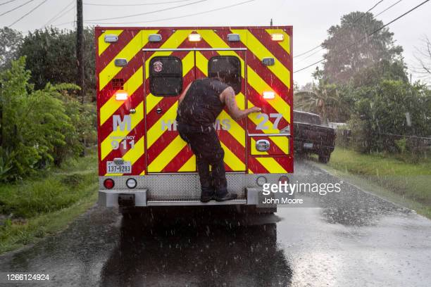 Man climbs up on an ambulance as EMS medics treat his mother inside before transporting her to a hospital on August 12, 2020 in Houston, Texas. The...