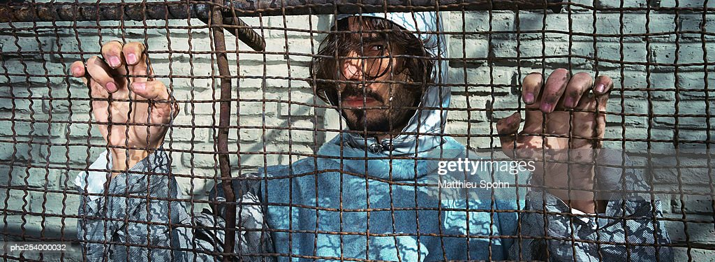 Man clinging on to wire netting : Stockfoto