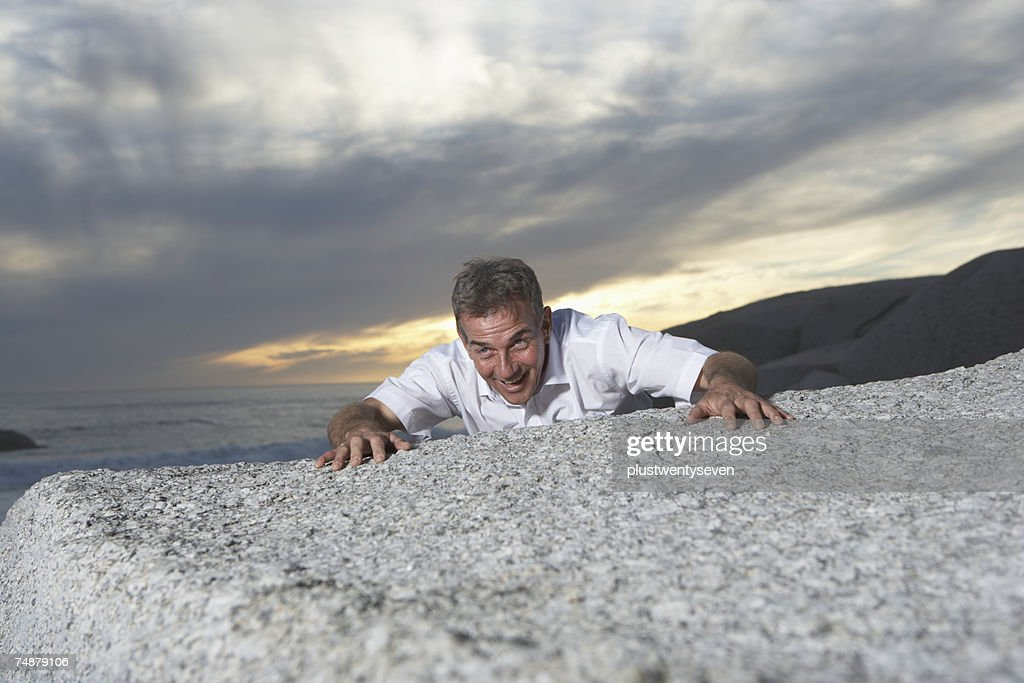 Man clinging onto rock on beach : Stock Photo