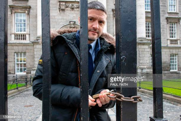 Man closes an entrance gate to Trinity College in Dublin on March 13, 2020. - Ireland on Thursday announced the closure of all schools and colleges,...