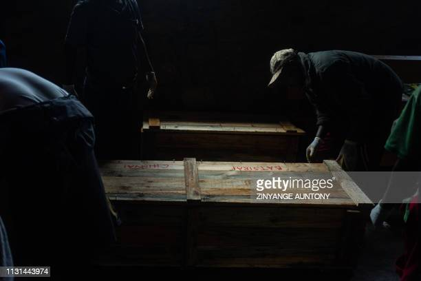 A man closes improvised caskets at the morgue on March 18 2019 in Chimanimani eastern Zimbabwe after the area was hit by the cyclone Idai A cyclone...