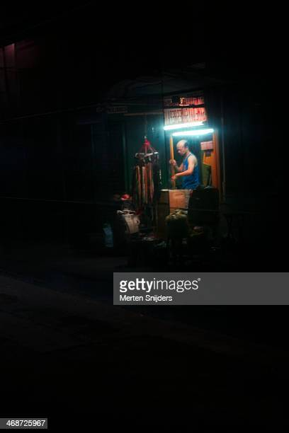 man closing down corridor shop at night - merten snijders stock pictures, royalty-free photos & images