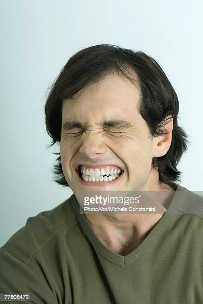 man closing eyes and clenching teeth, portrait - grimacing stock pictures, royalty-free photos & images