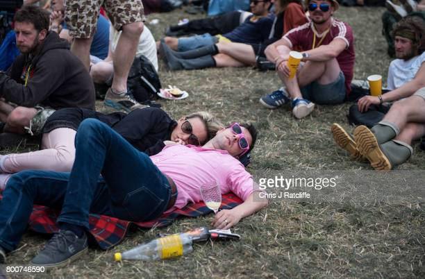A man clutches a wine glass whilst sleeping next to his partner during the afternoon at the Pyramid Stage at Glastonbury Festival Site on June 25...