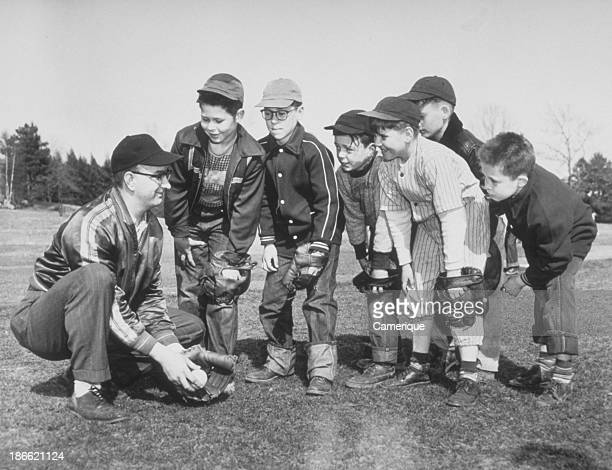 Man coach showing group of small boys how to catch a baseball grounder 1964