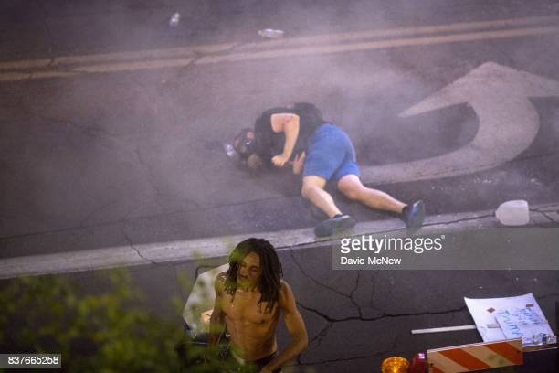 A man collapses as police pepper spray and tear gas demonstrators after a rally by President Donald Trump at the Phoenix Convention Center on August...