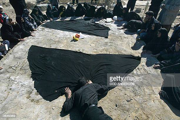 A man collapses on the grave containing 18 family members during a funeral service at the cemetery in the earthquake stricken Iranian city of Bam 01...