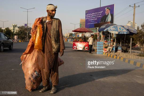 Man collecting cans for recycling walks by a Ghani campaign billboard in Kabul, Afghanistan on September 27, 2019. Afghans will head to the polls...