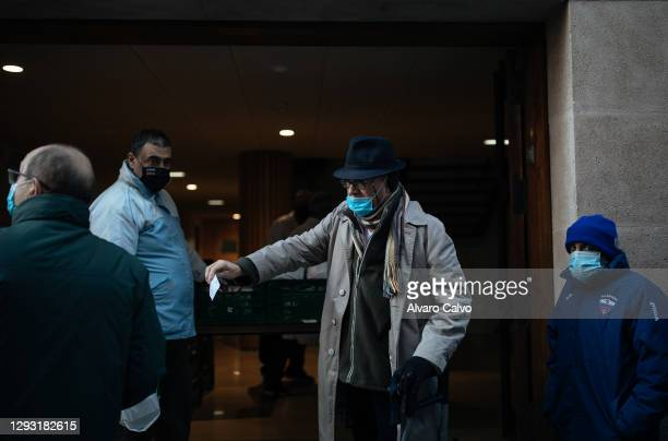 Man collects a tupperware with food from the soup kitchen in the parish of Carmen on Christmas Day. Due to the restrictions caused by the pandemic,...