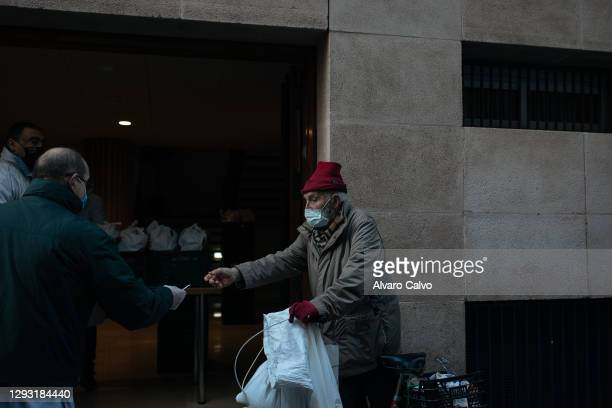 Man collects a tupperware with food from the soup kitchen of Carmen parish on Christmas Day, due to the restrictions of the pandemic, the soup...