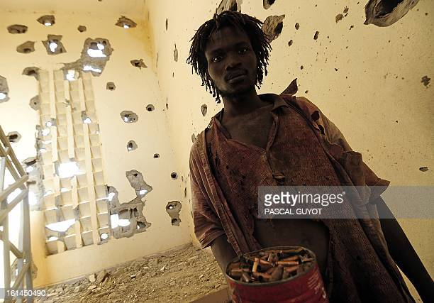 A man collects cartridge cases at a damaged police station one day after Islamist gunmen battled French and Malian troops following two straight days...