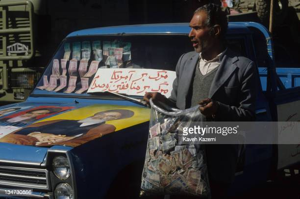 A man collects cash donations for troops on the IranIraq front outside Tehran University during a ceremony for the 7th anniversary of the Iranian...