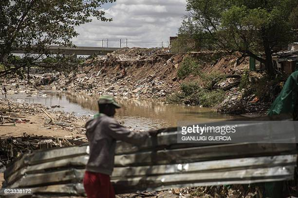 A man collects corrugated iron on the bank of a water stream in Alexandra Township an area affected by the recents floods on November 15 2016 in...