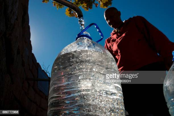 A man collects drinking water from taps that are fed by a spring in Newlands on May 15 in Cape Town South Africa's Western Cape region which includes...