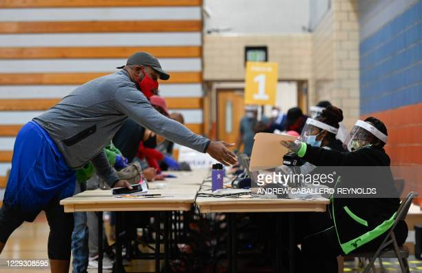 Man collects his ballot at Morgan State University, on the second day of early voting in the US presidential race, in Baltimore, Maryland on October...