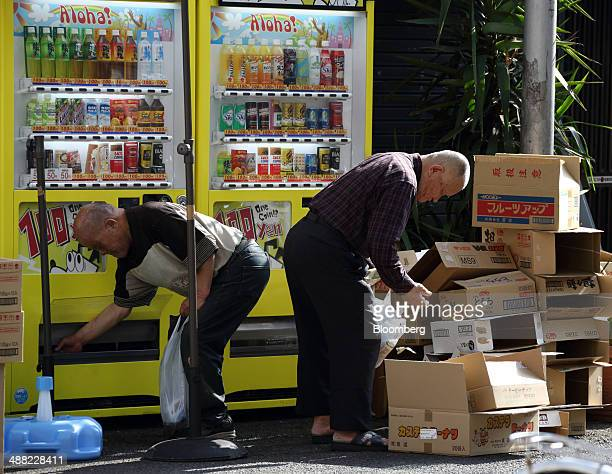 A man collects his drink from a vending machine as another checks cardboard boxes stacked in the Airin area of Nishinari ward in Osaka Japan on...