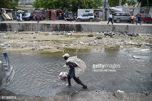 A man collects plastic and glass bottles in the canal of Portail Leogane in the Haitian capital PortauPrince on October 1 2016 As Hurricane Matthew...
