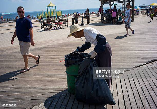 A man collects returnable bottles along the boardwalk July 24 2015 at Coney Island Beach in the Brooklyn borough of New York